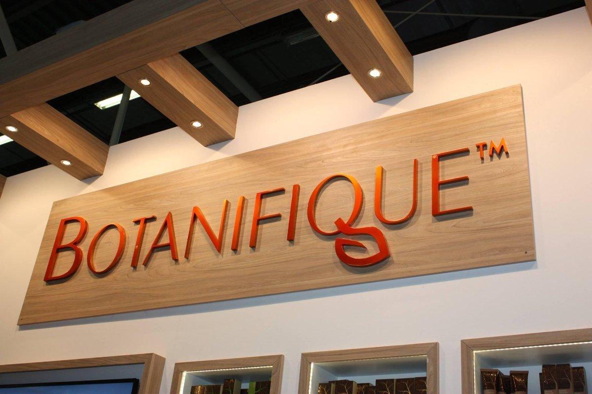Botanifique skincare signage is no lit letter on wood grain veneer panel.
