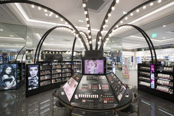 The round cosmetics display table with acrylic desktop display units and many TV at all sides